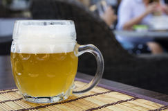 Glass mug of unfiltered weizen beer on table Stock Photography