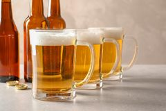 Glass mugs of cold tasty beer. On table royalty free stock photo