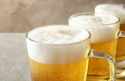 Glass mugs of cold tasty beer on table. Closeup stock photography