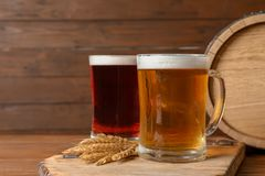 Glass mugs with different types of cold tasty beer. On wooden table stock image