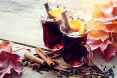 Glass mugs of mulled wine on wooden table with fallen maple leaves. royalty free stock photography