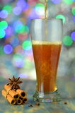 Glass of mulled spiced beer on bokeh background Royalty Free Stock Photography