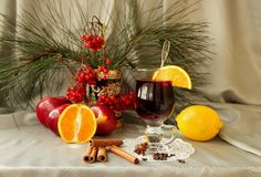Glass of mulled wine, apples, oranges, cinnamon sticks and spices Stock Photo