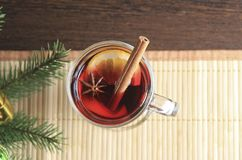 A glass of mulled wine is on a bamboo napkin. A sprig of Holly. New year`s drink royalty free stock photography