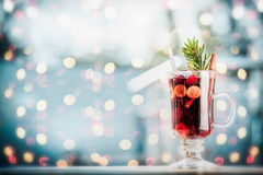 Glass of mulled wine with berries and fir branch on table at frosty winter day background with festive bokeh lighting background. Royalty Free Stock Photos
