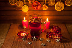 Glass of mulled wine and Christmas decorations, candles, gifts Royalty Free Stock Images