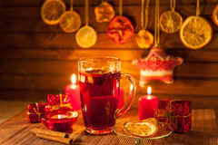 Glass of mulled wine and Christmas decorations, candles, gifts Stock Photo