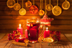 Glass of mulled wine and Christmas decorations, candles, gifts Royalty Free Stock Photography