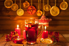 Glass of mulled wine and Christmas decorations, candles, gifts Stock Image