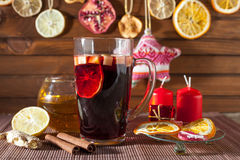 Glass of mulled wine and Christmas decorations, candles, gifts Stock Photos