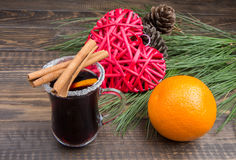 A glass of mulled wine and Christmas decorations on a dark wooden background Royalty Free Stock Image