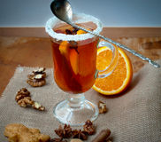 Glass of mulled wine with cinnamon and anise star. Mulled wine with cinnamon and star anise with slice of orange and spices and Christmas cakes, with decorated Royalty Free Stock Photo