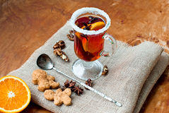 Glass of mulled wine with cinnamon and anise star. Mulled wine with cinnamon and star anise with slice of orange and spices and Christmas cakes, with decorated Royalty Free Stock Images