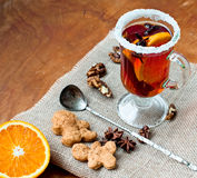 Glass of mulled wine with cinnamon and anise star. Mulled wine with cinnamon and star anise with slice of orange and spices and Christmas cakes, with decorated Stock Image