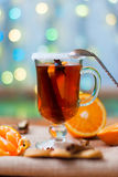 Glass of mulled wine with cinnamon and anise star. Mulled wine with cinnamon and star anise with slice of orange and spices and Christmas cakes, with decorated Stock Photography