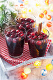 Glass of mulled wine with cranberry and spices, winter drink Stock Photos
