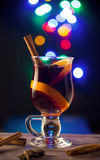 Glass with mulled wine on dark background with lights. Glass with hot wine on dark background with bokeh effect Stock Image