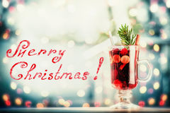 Glass of mulled wine and fir branch on table at frosty winter day background with festive bokeh lighting background and handwritin Stock Photos