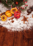 Glass of mulled wine and orange on a snowy table Royalty Free Stock Image
