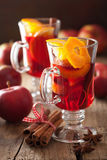 Glass of mulled wine with orange and spices, winter drink Stock Photos