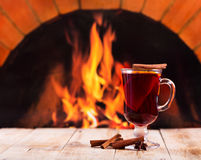 Glass of mulled wine  over fireplace Royalty Free Stock Image
