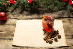 Glass of mulled wine with spices and christmas tree branches Stock Photos