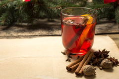 Glass of mulled wine with spices and christmas tree branches Royalty Free Stock Photos