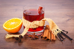 Glass of mulled wine wrapped scarf with fresh fragrant spices Royalty Free Stock Photo