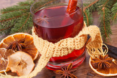 Glass of mulled wine wrapped scarf, spices and spruce branches Stock Photos
