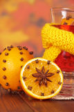 Glass of mulled wine in yellow scarf close-up Stock Image