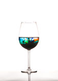 Glass with multicolored water on white background Royalty Free Stock Image