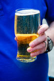 Glass mycket av öl i hand Arkivbild
