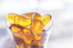 Glass mycket av kapslar för olja för torsklever Royaltyfri Foto