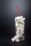 Glass mycket av sockerkuber med sugrör royaltyfria bilder