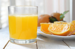 A glass of natural oranges served next to some slices. On a white wooden table Stock Photos