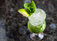 Glass with non-alcoholic mojito on marble table. Glass with non-alcoholic refreshing mojito on marble table Royalty Free Stock Photos