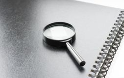 Glass on Notes. Black magnifying glass on black notebook, angle view, office background Stock Photo