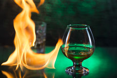 Glass o whisky with ice and wineglass of cognac and fire flames on green bokeh background Royalty Free Stock Image
