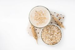 Glass of oat milk and grains in white bowl. Isolated on white background royalty free stock image