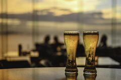 Free Glass Of Beer A Shadow On The Sky Bar Counter In Restaurant. Draft Beer In Happy Hour Buy 1 Get 1 Free. Royalty Free Stock Photo - 180276215