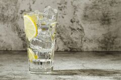 Free Glass Of Clear Water With Ice And Lemon On A Gray Background. Close-up. Copy Space. Stock Images - 173146774