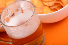 Glass Of Light Beer And Potato Chips On A Wooden Table Stock Photo