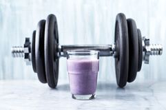 Glass Of Protein Shake With Milk And Blueberries And A Dumbbell In Background. Sports Bodybuilding Nutrition. Stock Photo