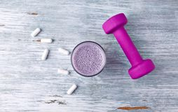 Glass Of Protein Shake With Milk And Blueberries. BCAA Amino Acids And A Violet Dumbbell In Background. Sport Nutrition. Stock Photography