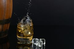 Free Glass Of Whiskey With Splash, On A Black Background. Old Barrel. Ice Royalty Free Stock Image - 157973036