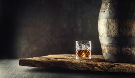 Free Glass Of Whisky Or Bourbon In Ornamental Glass Next To A Vinatge Wooden Barrel On A Rustic Wood And Dark Background Stock Photography - 213308352