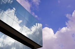 Glass office building. Modern glass office building reflecting clouds and blue sky mirror finish Stock Photography