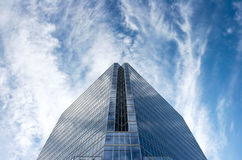 Glass Office Building In Huge Blue Sky. Office tower set against deep blue sky with white cirrus clouds Royalty Free Stock Image