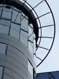 Glass office building parapet detail and design feature. View of circular office building tower and parapet and design features in glass curtain wall Stock Image