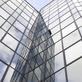 Glass office facade reflects clouds and blue sky Royalty Free Stock Photography
